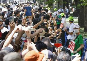 沿道で女子個人ロードレースを観戦する人たち=25日、東京都府中市