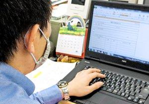 見守りが必要な子どもに関する資料を確認する小学校教員(京都市内)