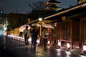あんどんに照らされ、雨でしっとりとぬれた石畳を歩く人々(6日午後7時30分、京都市東山区・ねねの道)