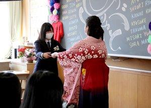 担任が黒板に描いたイラストの前で卒業証書を受け取るマスク姿の卒業生(東近江市横溝町・湖東中)