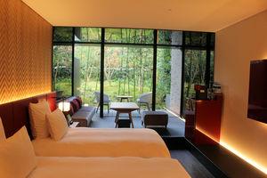 庭園の風景を鏡面仕上げの壁が取り込む客室(京都市中京区)