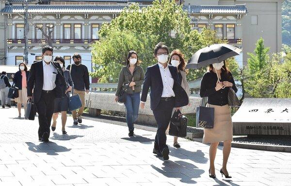 大型連休が明け、足早に職場などに向かう人たち(7日午前8時17分、京都市・四条大橋)