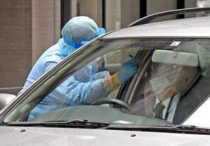 ドライブスルー方式による検体採取のデモンストレーションを行う京都市職員ら。認知症の人にとっては検査を受けることにも難しさが伴う(4月27日、京都市中京区・市役所)
