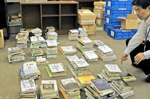 宇治市の林道沿いに投棄されているのが見つかった図書館の書籍。図書館職員らは分類作業に追われた(同市折居台・市中央図書館)