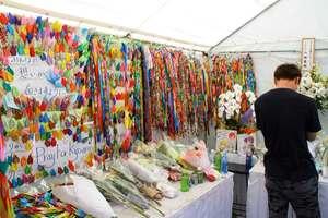 5万羽以上の折り鶴が飾られた献花台で、犠牲者を悼む男性(8日午前11時20分、京都市伏見区)