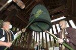 ササの葉と竹で作ったほうきで、梵鐘のほこりを払う僧侶たち(28日午前10時7分、大津市園城寺町・三井寺)