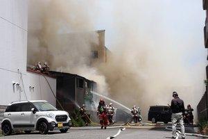 大量の煙を出す建物に放水活動をする消防隊員ら(17日午前11時15分、京都市南区)