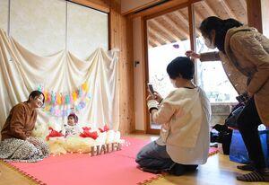 クリスマスケーキをイメージした装飾が施された一角で、写真に収まる赤ちゃんと母親(守山市勝部2丁目・勝部自治会火まつり交流館)