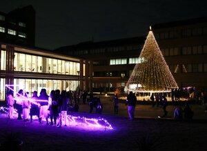 電飾されたシンボルツリーの前で記念撮影する学生たち(京田辺市興戸・同志社女子大)