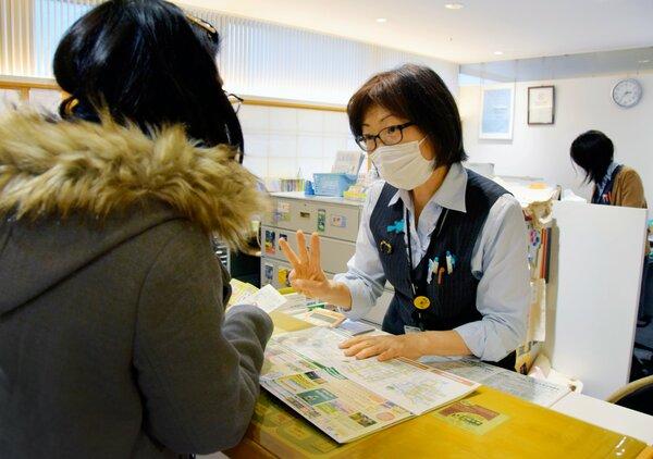 感染を防ぐため、マスクを着用して観光案内に当たる京都総合観光案内所の職員(下京区・京都駅ビル)