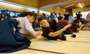 素早い手さばきでかるたを払い取る女性選手(京都市右京区・嵯峨嵐山文華館)