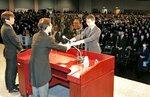 2年ぶりとなる卒業式で、湊総長(中央)から学位記を受け取る卒業生(24日午前、京都市左京区・みやこめっせ)