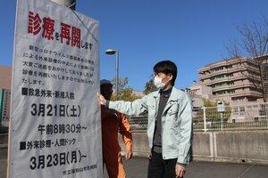 外来診療などの再開を知らせるため、福知山市民病院前に看板を設置する職員ら(福知山市厚中町)