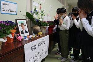 肺がんで亡くなった宇佐恒浩前校長の遺影が置かれた献花台に向かって、手を合わせる児童(草津市・玉川小)