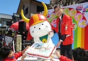 井伊会長(右奥)らに特大ケーキを贈られ喜ぶひこにゃん=滋賀県彦根市本町1丁目・四番町スクエア