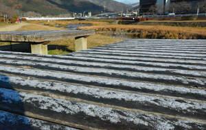 うっすらと雪が積もったベンチ(2020年12月16日午前8時半、京都市北区西賀茂の賀茂川)