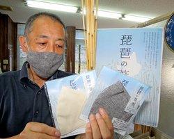琵琶湖岸のヨシ(中央奥)を素材に使ったマスクを着用する中村社長=高島市新旭町藁園