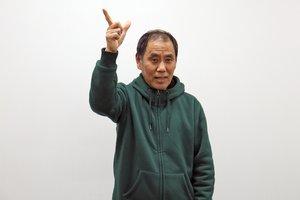 「明智光秀」を表す手話表現の一部。知将だった光秀をイメージし、頭の上で親指と人さし指を広げる(いずれも福知山市内記・ハピネスふくちやま)