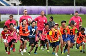 笑顔で児童と一緒に走るウェールズ代表チーム(4日午後5時5分、大津市御陵町・皇子山陸上競技場)