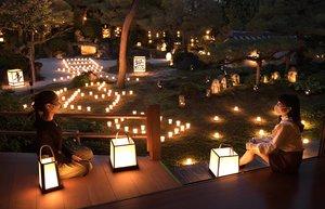 ろうそくの明かりに彩られ、「無事是好日」の文字が浮かぶ庭園(15日午後5時51分、京都市右京区・東林院)