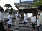 園部城の門の前で、養成講座の狙いなどを高校生に語る窪田教授(左から3人目)=南丹市園部町・園部高