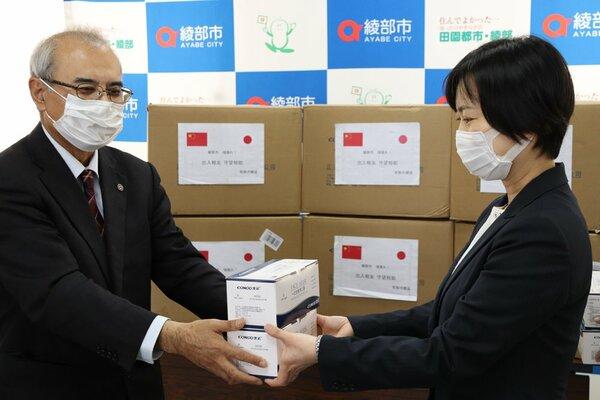 中国・常熟市から届いたマスク。足立教育長(左)が学校関係者に手渡した(綾部市若竹町・市まちづくりセンター)