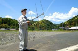 サルに取り付けられた発信器からの電波を手持ちアンテナを使って探す三野さん(伊根町大原)