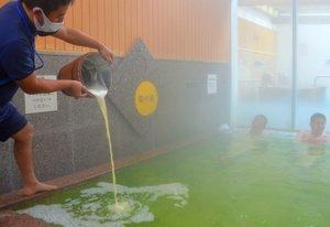 湯に生ビールを注ぐ担当者(京都府南丹市日吉町・道の駅「スプリングスひよし」)