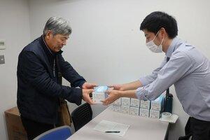 京都市の担当者(右)からマスクを受け取る介護事業所の担当者=中京区