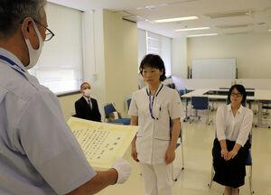 連携して男性の命を救ったとして表彰された津田さん(中央)と東山さん(右)=南丹市日吉町・明治国際医療大付属病院