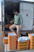 滋賀県野洲市学校給食センターから提供を受けた牛乳を積み込む「フードバンクびわ湖」の堀共同代表(同市八夫)