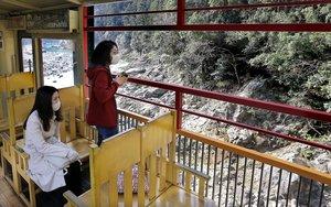 運行が始まったトロッコ列車からの景色を楽しむ観光客(1日午前9時13分、京都市右京区)