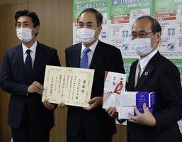 自社製マスクを寄付し、感謝状を手にするMTGの大田会長(中央)と松下社長(左)=京都市中京区・市役所