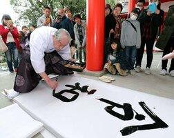 参拝者たちが見守る中、新元号を墨書きする佐藤宮司(1日午前11時43分、大津市神宮町・近江神宮)