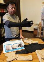 圧迫装具のサンプルを腕に装着する盛本さん。ケロイドなど皮膚の盛り上がりを予防する効果があるという(京都市内)