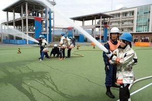 女性を対象にした消防士体験のイベントで、放水を体験する参加者たち(京都市南区・市消防活動総合センター)