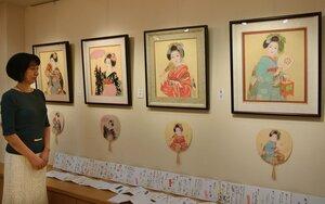 さまざまな表情の舞妓の絵が並ぶ「舞妓百態展」を見つめる吉田さん(京都市東山区・ギャラリー祇園小舎)