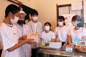 「敬老の日」限定のどら焼きセットを購入し、越田社長(左から2人目)から受け取る高校生(左端)。右側は商品を考案した大学生ら=精華町祝園西・御生菓子司ふたば
