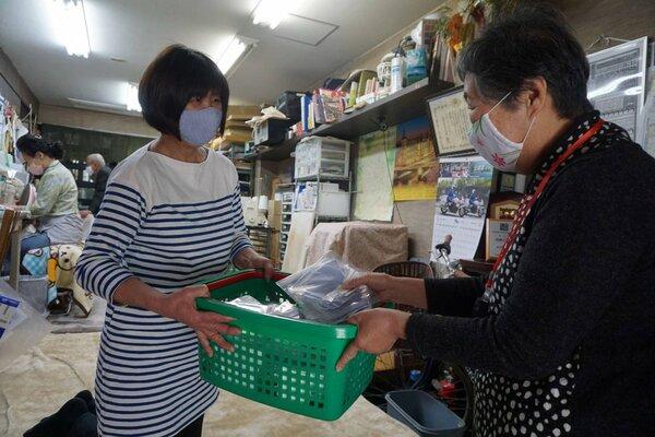 地域の高齢者に手作りマスクを手渡す梅屋自治連合協議会の紀平さん(左)=京都市中京区