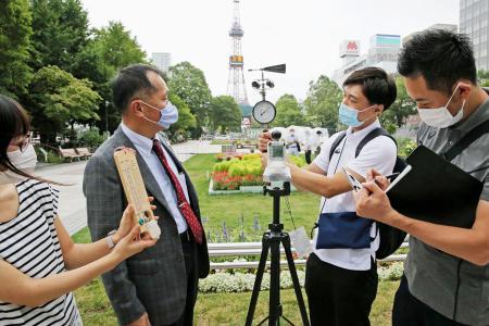 東京五輪マラソン・競歩会場の札幌市で始まった「実地検証」。大会組織委の森泰夫大会運営局次長(左から2人目)らが気温や風速を調べた=6日午後(代表撮影)