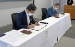 地方創生に関する連携協定にサインする若菜支社長(左)と福井市長=15日、高島市役所