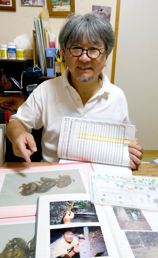 親子で26年間調査してきたセミの記録や写真を見せる井上さん。「これまでの調査結果を精査して、いつかまとめたい」と意気込む(京都市北区)