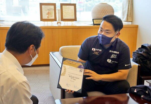 桂川市長(左)に賞状を見せながら熱気球のジュニア世界選手権の結果を報告する山下さん=亀岡市安町・市役所