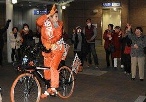 自転車で街中を走り、支持を訴える赤坂さん(25日夕、亀岡市・亀岡駅前)