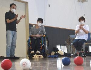 「oneボッチャ」を考案した田中さん(左)と、大会に向けて練習を積む参加者たち=野洲市冨波甲・市なかよし交流館