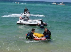 水上用の担架を使って水難者に見立てた人形を岸まで運ぶ京丹後署員(手前)=京丹後市網野町・八丁浜海水浴場
