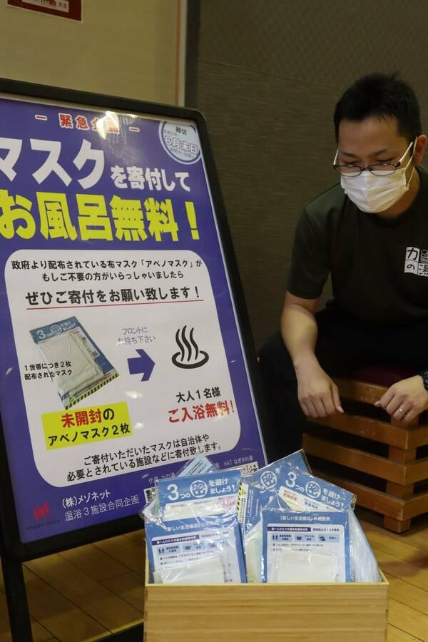 布マスクの寄付で入浴料が無料になるキャンペーンの案内と、既に集まったマスク(京都市伏見区・伏見力の湯)