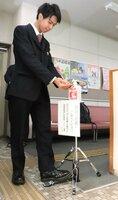 ボトルに触れずに噴霧できる消毒液スタンドと後藤さん(近江八幡市役所)