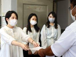 滋賀県議会事務局に請願を手渡す滋賀県立大の学生たち=滋賀県庁