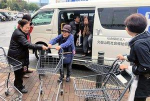 買い物に行く送迎サービス利用者に声を掛ける加賀爪さん(左)=久御山町森・イオンモール久御山